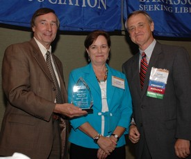 On behalf of the Johnston County Bar Association, Tom Berkau, left, and Cindy Pittard accept Chief Justice Award from NCBA President Gene Pridgen.